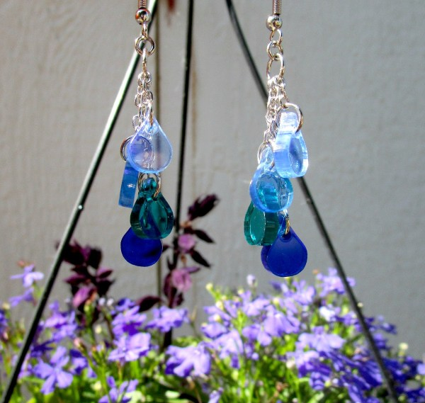 Blue Ocean Water Drops Earrings hanging with purple flowers and gray wall in background