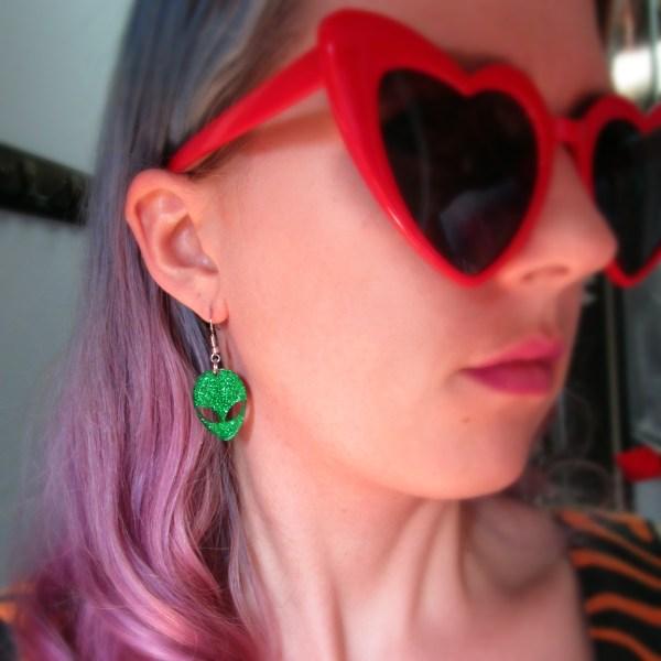 woman with heart glasses wearing glitter green alien face earring
