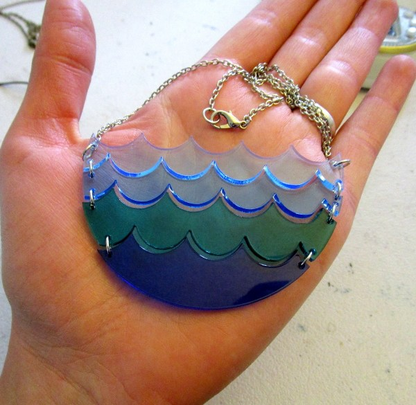 blue water wave necklace on palm of hand
