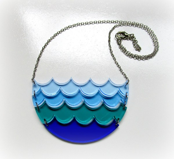 blue ocean wave statement necklace on white gray background with chain in curl showing lobster claw clasp