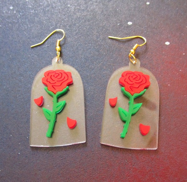 top view down on beauty and beast enchanted rose earrings with space background