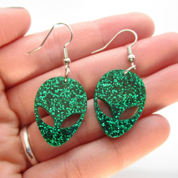 hand holding 2 green glitter alien head dangle earrings