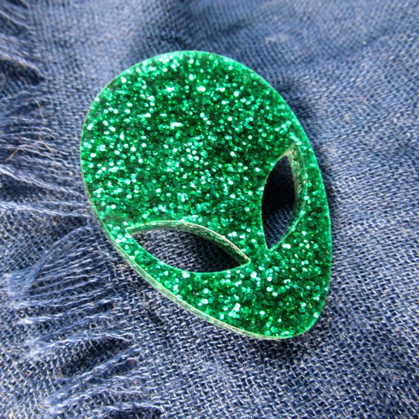 glitter green alien head brooch on dark blue fabric