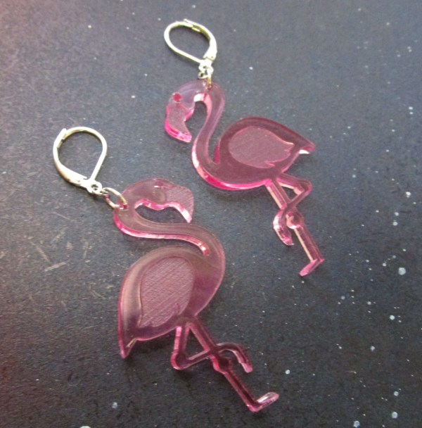 sideways view of pink flamingo statement earrings on space background