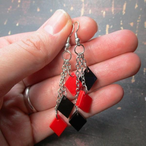 hand holding harley quinn diamond dangle earrings