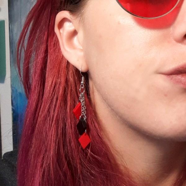 lady wearing harley quinn black and red diamond dangle cosplaay earrings