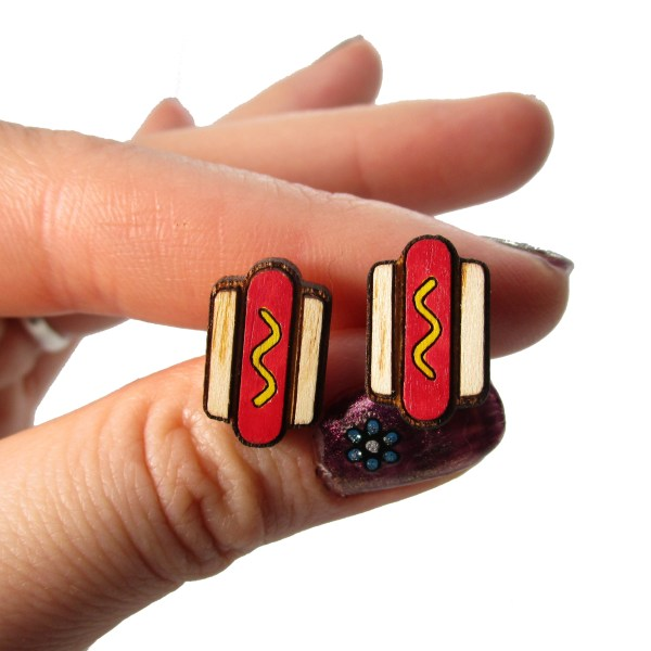 little miniature hotdog food earrings in hand to show size