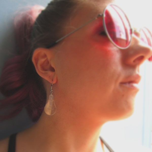 woman with red glasses wearing light bulb shaped dangle earrings