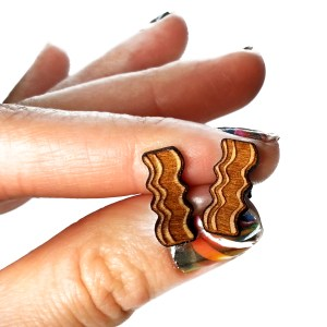 hand holding bacon earrings to show size