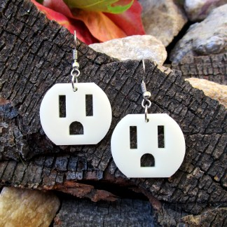 electrical outlet face earrings on wood bark background