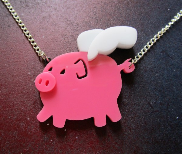 flying pig pink pendant with silver chain close up shot