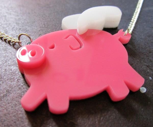 side close up shot of pink flying pig pendant necklace