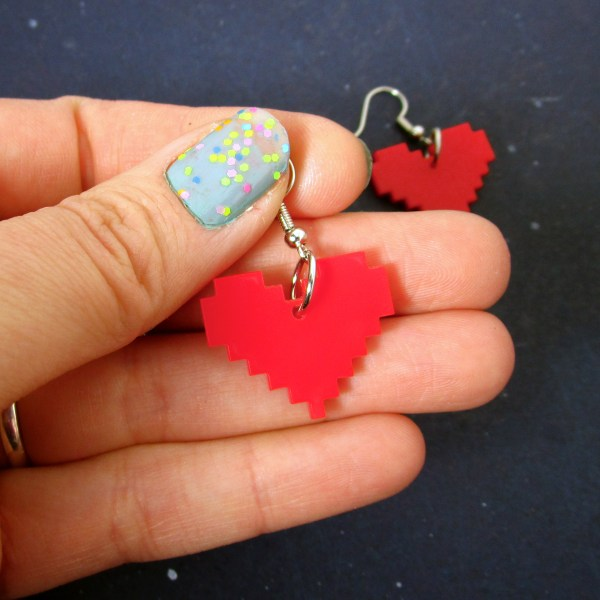 hand holding red 8 bit pixel heart dangle earrings