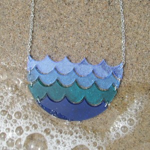 blue ocean wave pendant necklace on sand with water bubbles