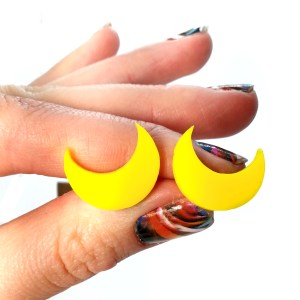 hand holding crescent moon earrings to show size, yellow moons