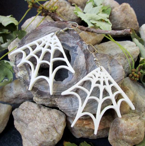 white spider web earrings on rocks
