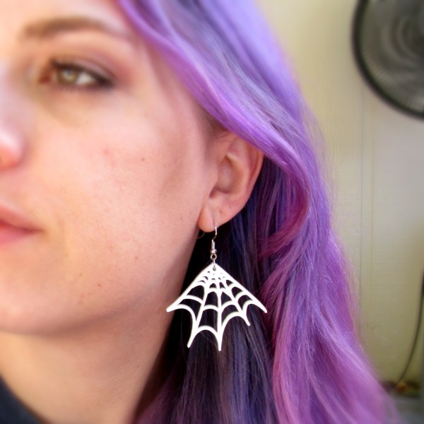 purple hair lady close up of ear with white spider web earring