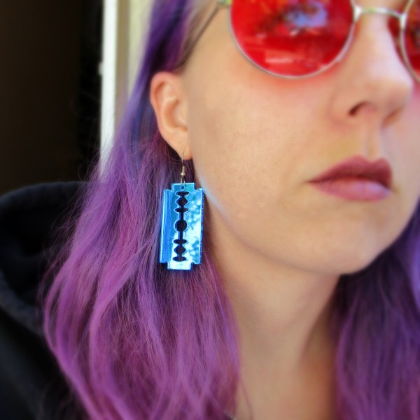 purple hair lady wearing blue razor blade earring