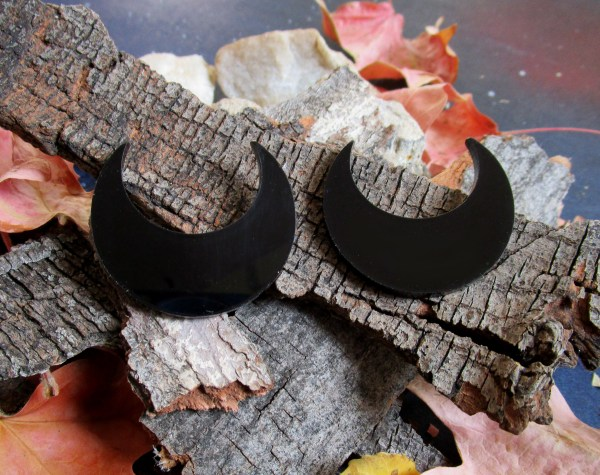 big black crescent moon earrings on bark background