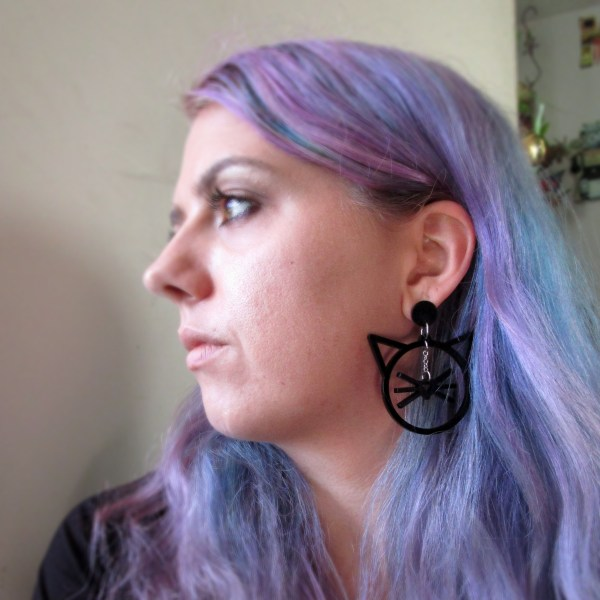 purple hair lady wearing big cat shaped whisker dangle stud earrings