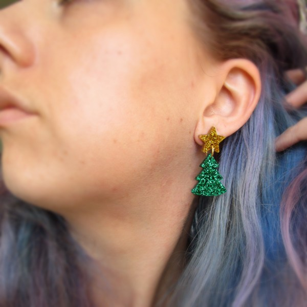 woman wearing a christmas tree earring in ear