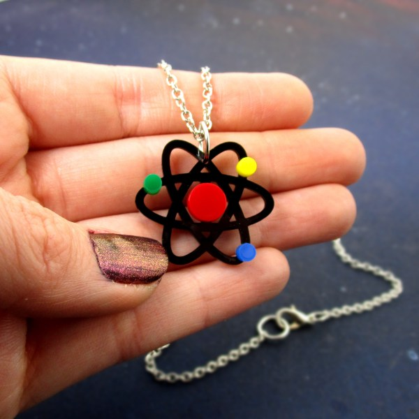 atom pendant on chain in hand