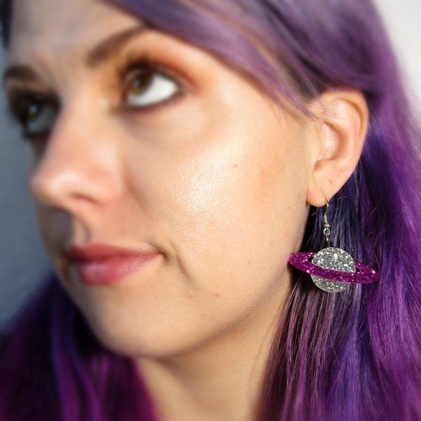 lady wearing silver and purple plant earrings