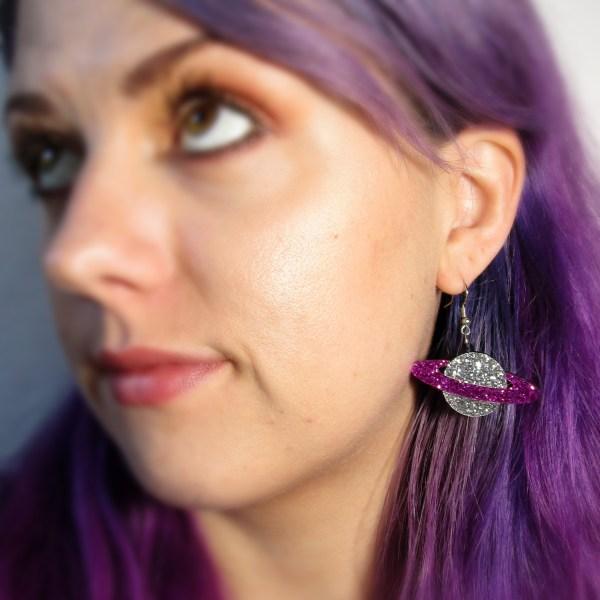 lady wearing silver and purple plant earrings