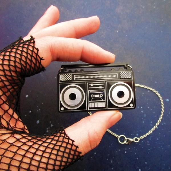 hand holding boom box radio pendant necklace to sho size