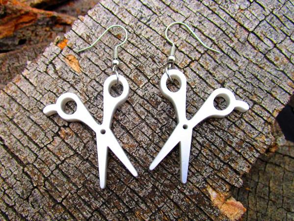 silver scissor earrings on wood background