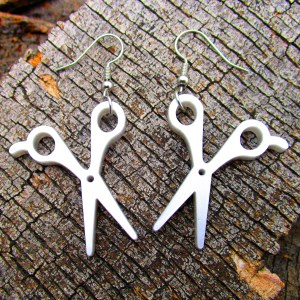 silver scissor earrings on wood background