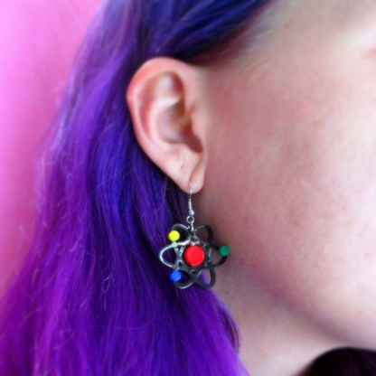 purple hair lady wearing atom dangle earrings