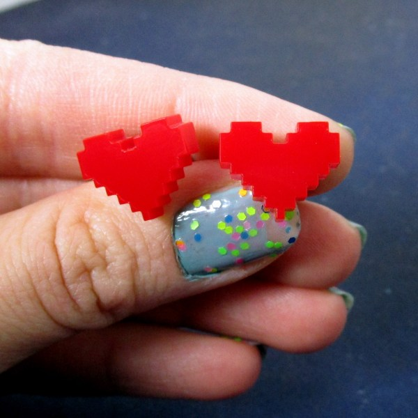 hand holding pixel heart stud post earring for size
