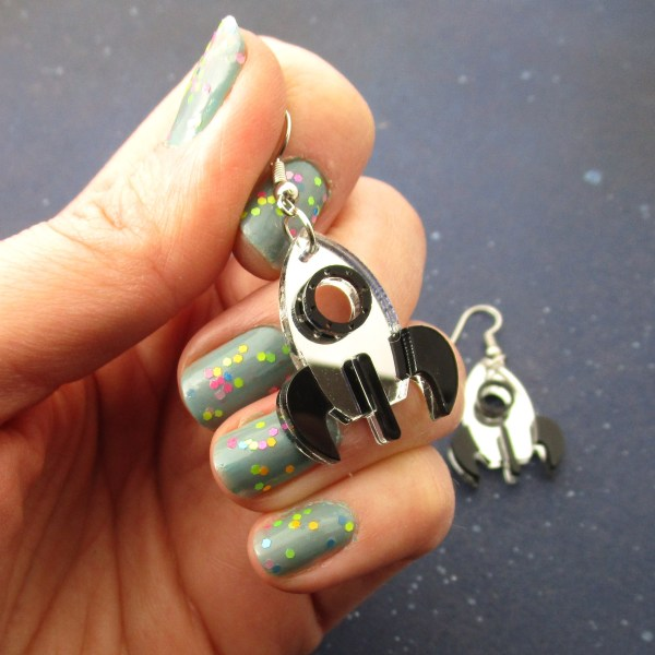 hand holding space rocket statement earrings