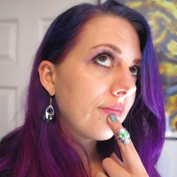 purple hair lady wearing rocket ship dangle earrings