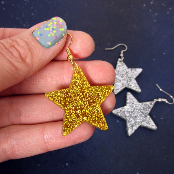 hand holding one gold star dangle earrings with glitter silver earrings in distance