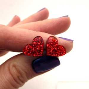 hand holding glitter red heart studs for valentines day