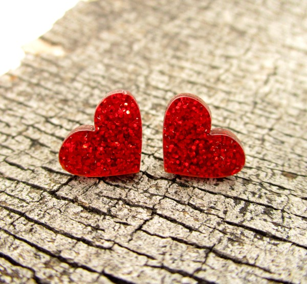 bright red glitter heart earrings on wood background