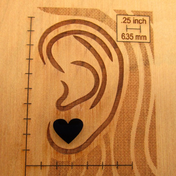 black heart stud earring on wooden ear display to show size