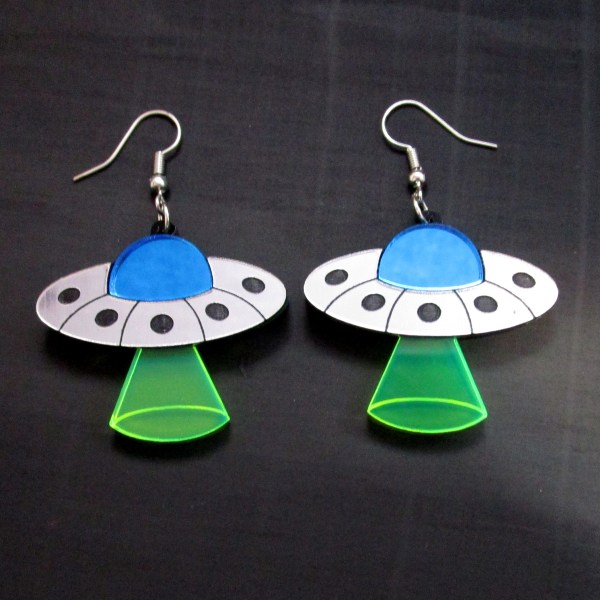 flying saucer earrings on black background