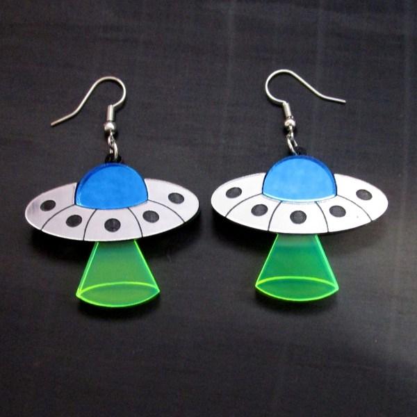 flying saucer earrings on black background