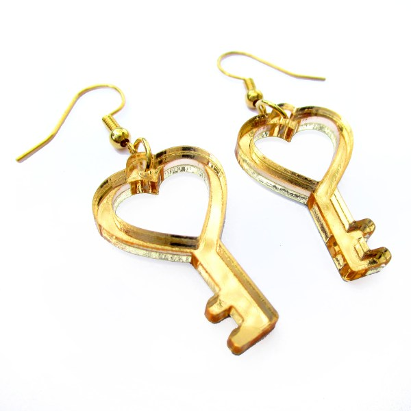 side view of mirrored gold acrylic little heart key dangle earrings