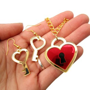 hand holding heart key earrings and heart lock neckalce to show size
