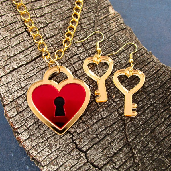 heart lock necklace and heart key earrings on wood background