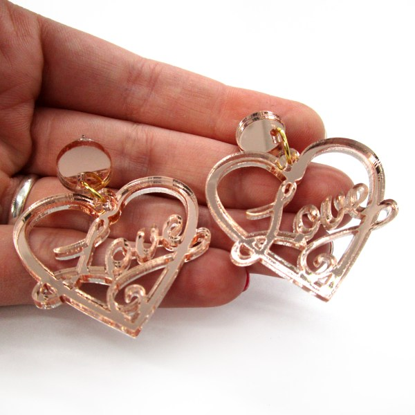hand holding love heart earrings to show size