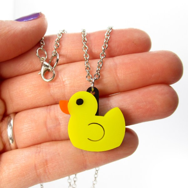 hand holding yellow duck rubber toy necklace