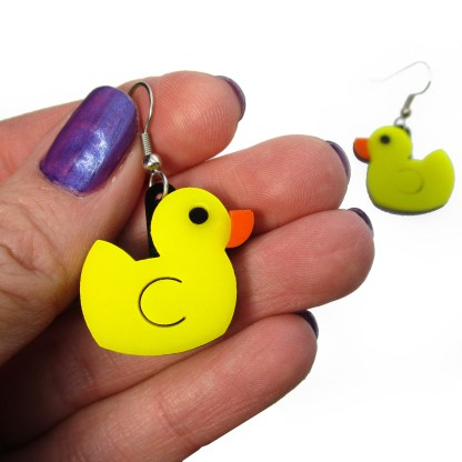 hand holding yellow rubber duck statement earring to show size