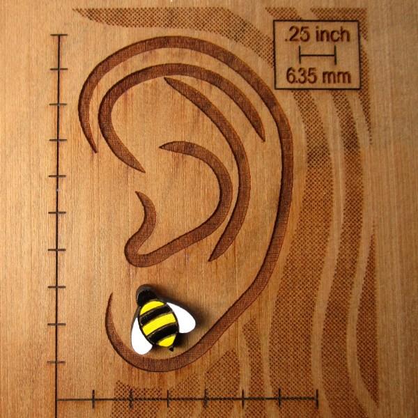 bee earring on ear board to show size