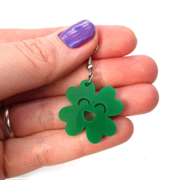 hand holding happy st patricks day clover earring to show size