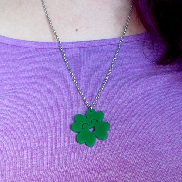 woman wearing clover necklace on purple shirt